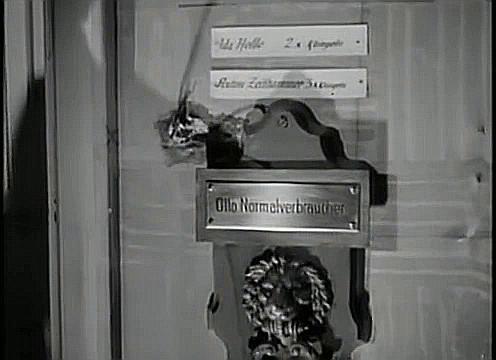 """Schwarzweißaufnahme von einem Türknauf mit einem Messing-Türschild, auf dem """"Otto Normalverbraucher"""" zu lesen ist"""